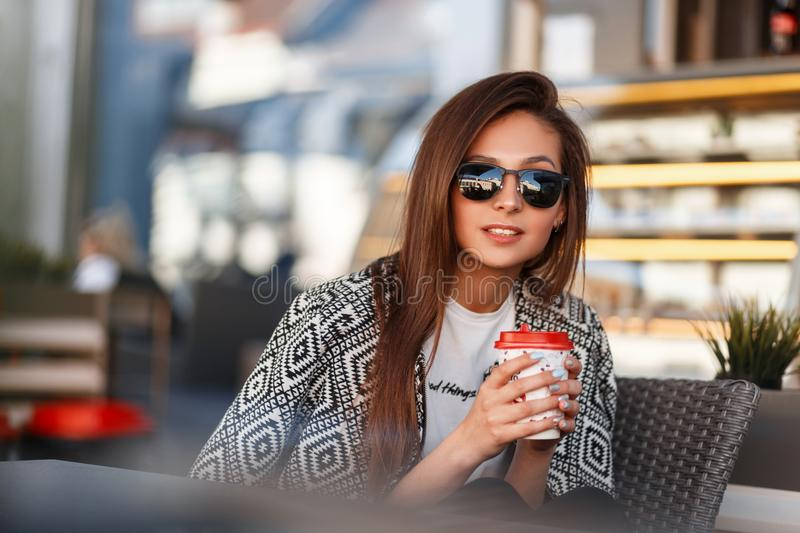Beautiful young girl with coffee in sunglasses sits royalty free stock images