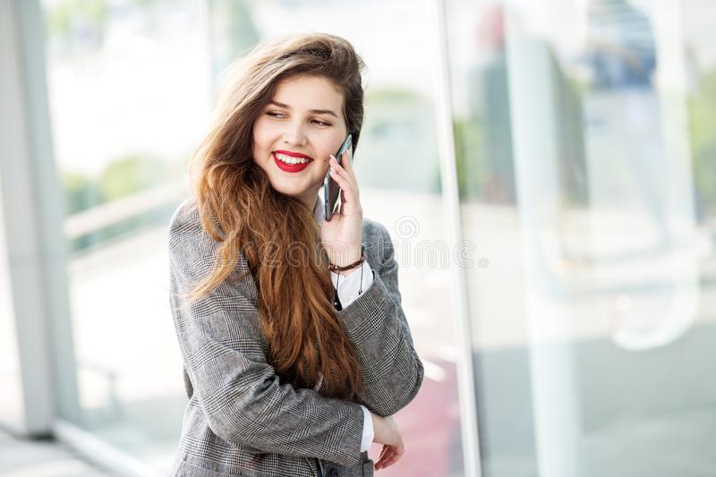 Beautiful young girl communicates on the smartphone. Red lipstick. The concept of fashion, business, communication and lifestyle royalty free stock photos