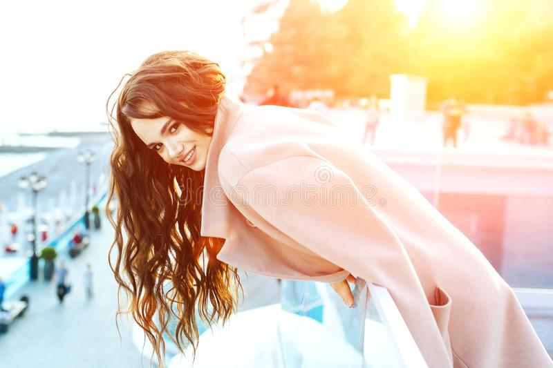 Beautiful young girl with dark hair stands near the sea in a beige coat and smiles. royalty free stock images