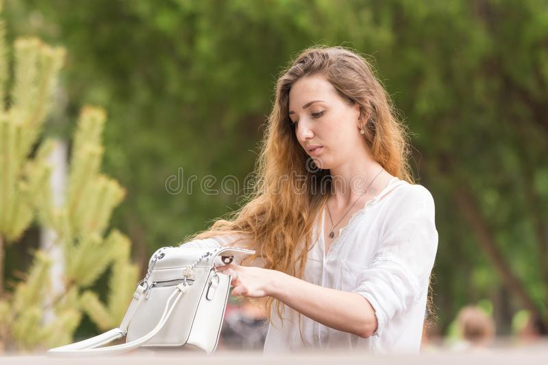 Beautiful young girl is delving into her purse in park stock images