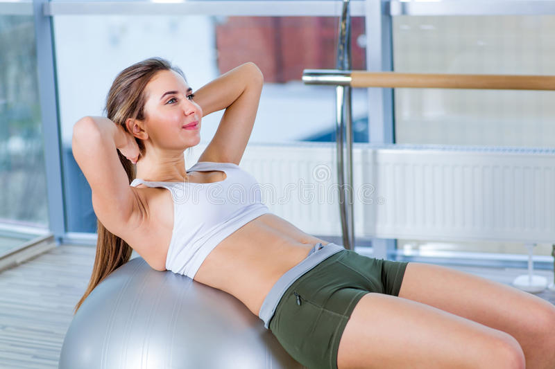 Beautiful young girl doing exercises with fit ball at gym. royalty free stock photography