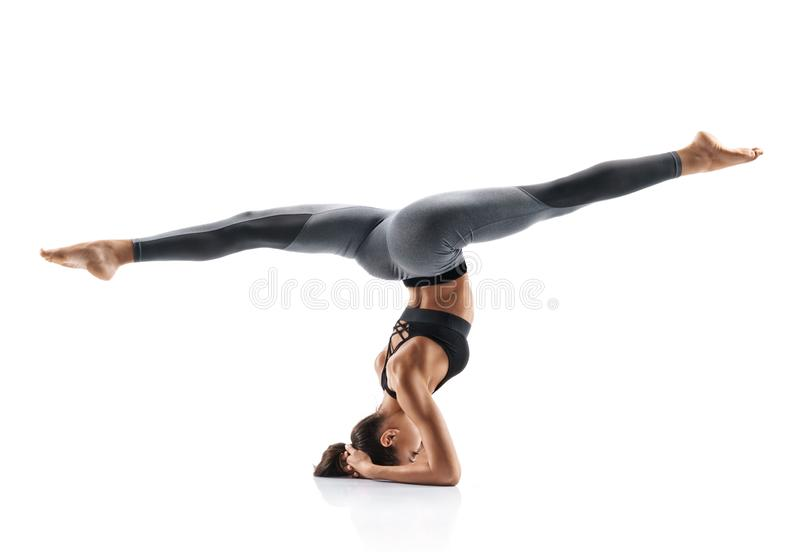 Beautiful young girl doing yoga or pilates exercise isolated on white background. stock image