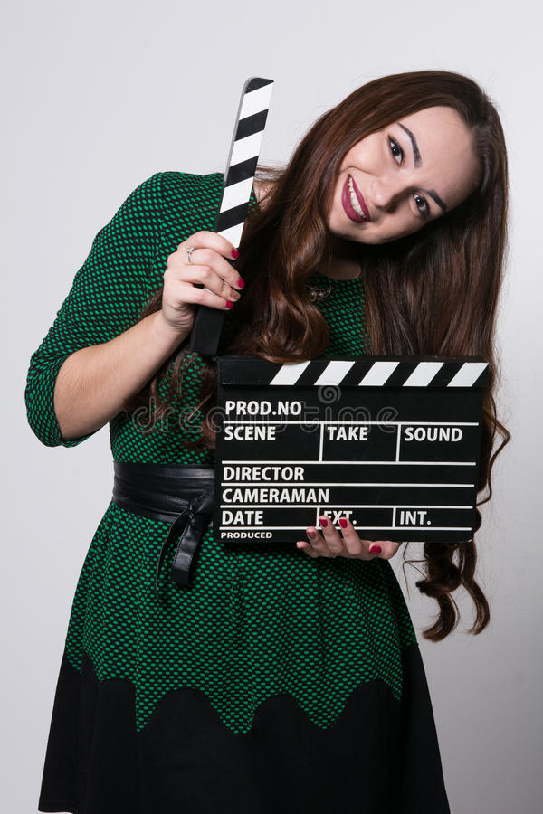 Beautiful young girl in dress is holding a clapperboard. Looking at camera and smiling, standing against blackboard stock image