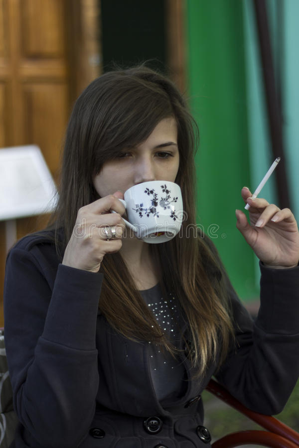 Beautiful young girl drink coffee and smoke cigar royalty free stock images