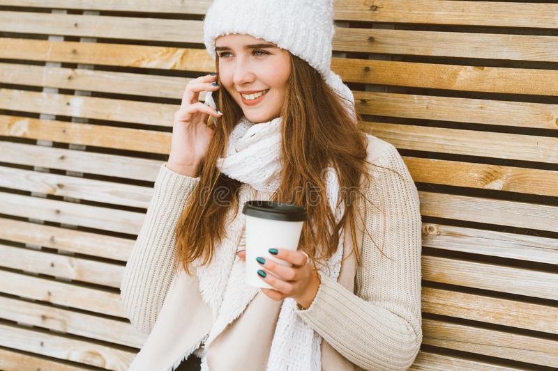 Beautiful young girl drinking coffee, tea from plastic mug in autumn, winter and talking on mobile phone. Woman with long hair. Beautiful young girl drinking stock photos