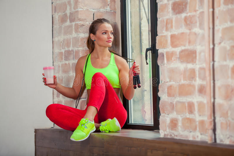 Beautiful young girl is drinking a fitness smoothie. Healthy lifestyles concept. royalty free stock photo