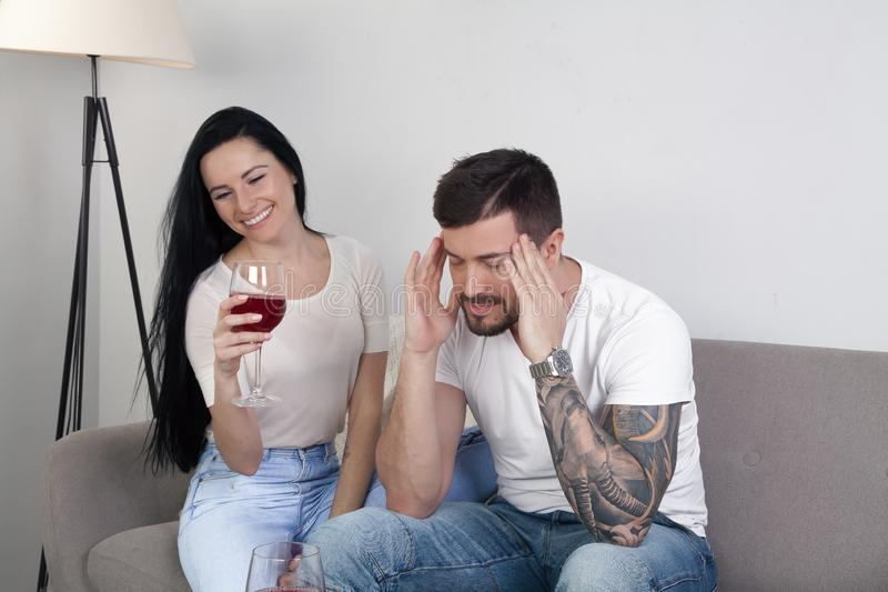 Beautiful young girl drinking wine sitting on the couch, and her boyfriend is sitting frustrated. He has a headache royalty free stock photos