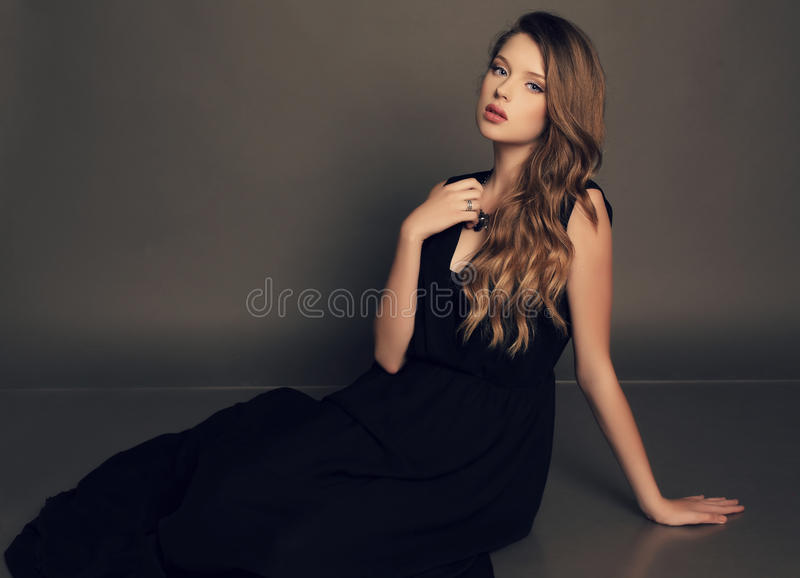 Beautiful young girl in elegant black dress with bijou. Fashion studio photo of beautiful young girl with dark natural hair wearing black dress and bijou stock images