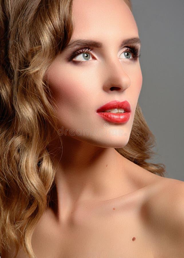 Beautiful young girl with an evening makeup and long blond hair. royalty free stock photos