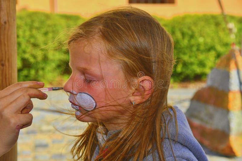 Beautiful young girl with face painted like a rabbit. Face painting on child face stock photos