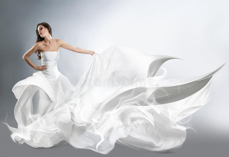 Beautiful young girl in flying white dress. royalty free stock photography