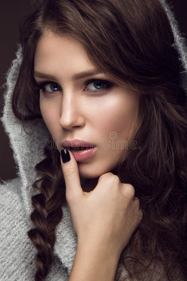 Beautiful young girl with gentle make-up in warm sweater and long straight hair. Beauty face. stock image