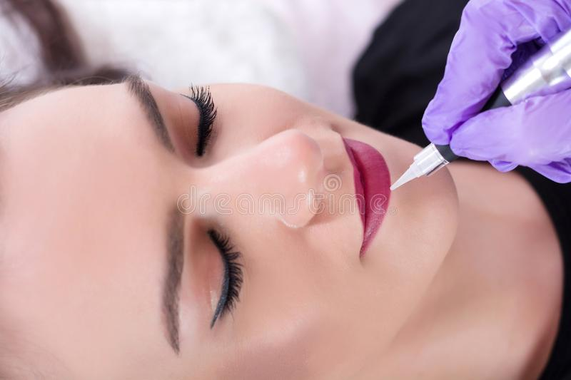 Beautiful young girl getting tattoo red lips in beauty studio. Professional cosmetologist making permanent make up with tool in purple gloves. Close up royalty free stock images