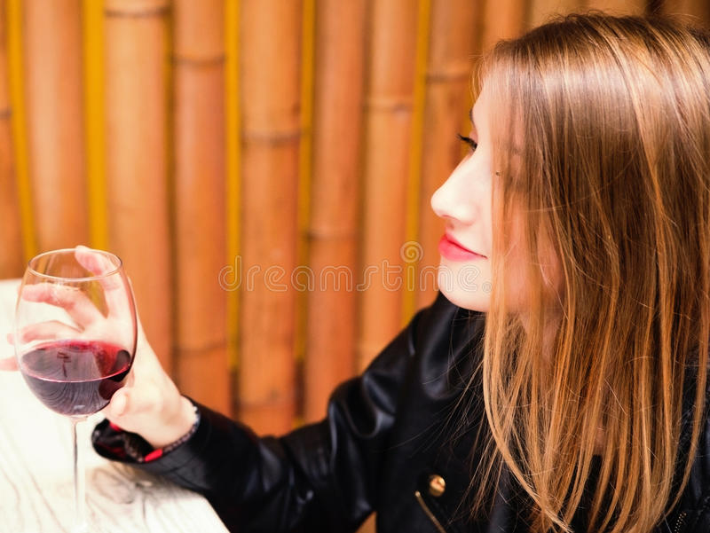 Beautiful young girl with glass of red wine royalty free stock photography