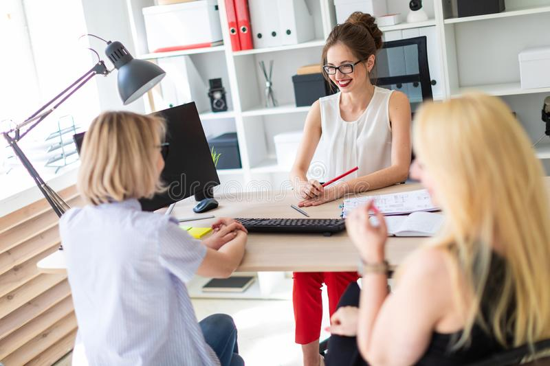 A young girl sits at a table in her office and talks to two co-partners. The girl is holding a pencil in her hand and. Beautiful young girl in glasses and a red stock image