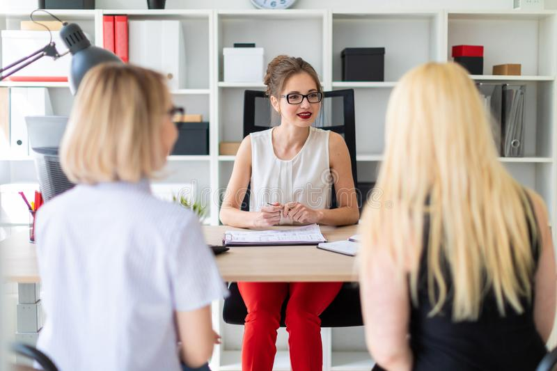 A young girl sits at a table in her office and talks to two co-partners. Beautiful young girl in glasses and a red shirt is working in the office. photo with royalty free stock images