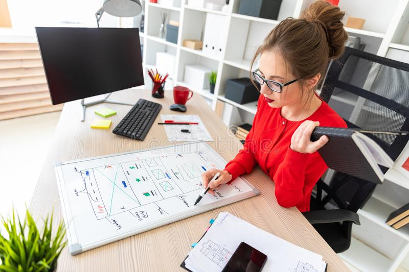 A young girl sits at a table in the office, holds a marker in her hand and works with a notepad and a magnetic board. Beautiful young girl in glasses and a red royalty free stock photos