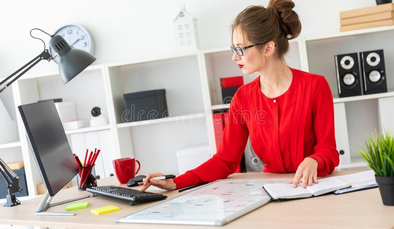 A young girl sits at a table in the office and holds a black marker in her hand. The girl works with a computer, notepad. Beautiful young girl in glasses and a stock photography