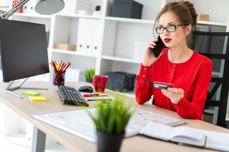 A young girl is sitting at the desk in the office, holding a bank card and phone in her hand. Beautiful young girl in glasses and a red shirt is working in the royalty free stock image