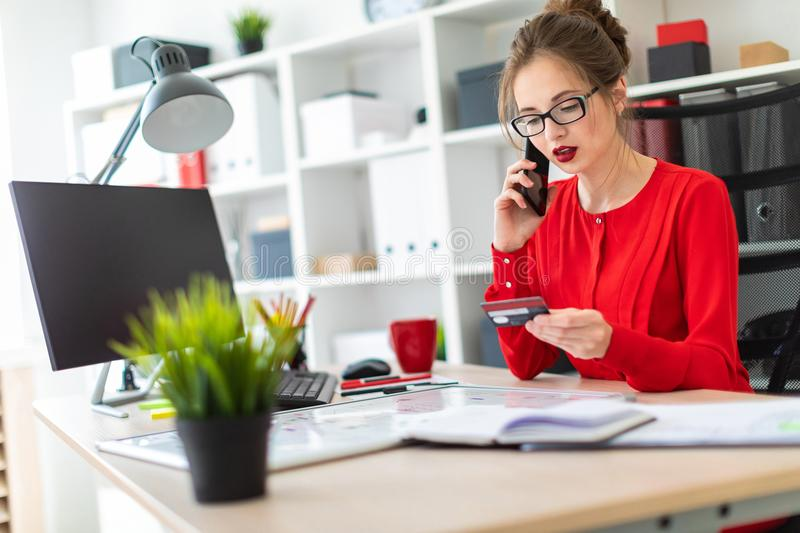 A young girl is sitting at the desk in the office, holding a bank card and phone in her hand. Beautiful young girl in glasses and a red shirt is working in the stock photo