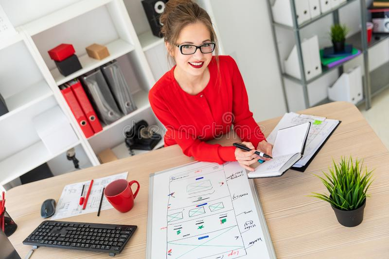 A young girl is sitting at the desk in the office, holding a black marker in her hand and working with a notepad. A. Beautiful young girl in glasses and a red royalty free stock photography