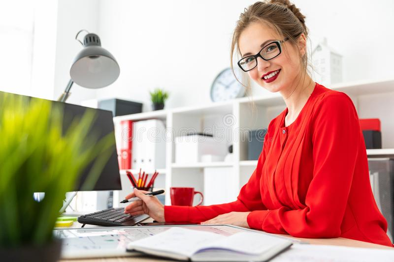 A young girl stands at a table in the office and holds a black marker in her hand. Beautiful young girl in glasses and a red shirt is working in the office royalty free stock photography
