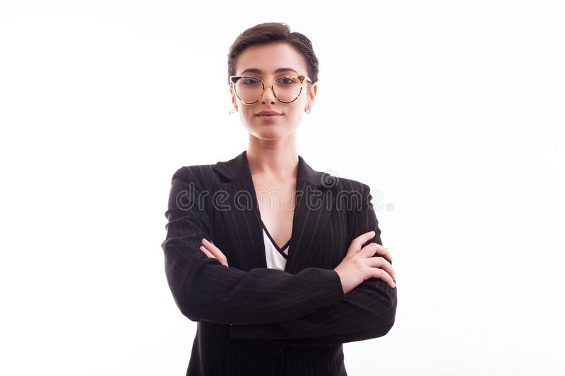 Beautiful young girl with glasses and short hair wearing a black jacket with hands crossed over white background in royalty free stock photo