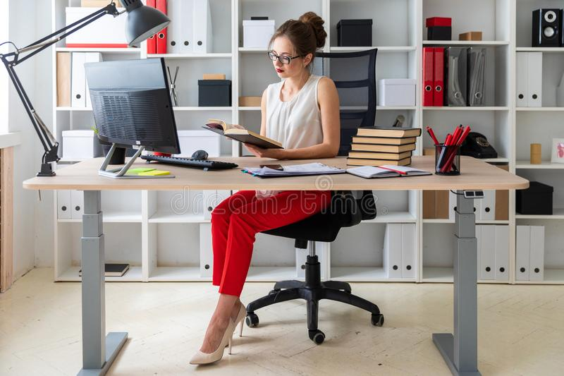 A young girl sits at a computer table and holds an open book in her hands. Beautiful young girl in glasses and a white blouse is working in the office. photo stock photography