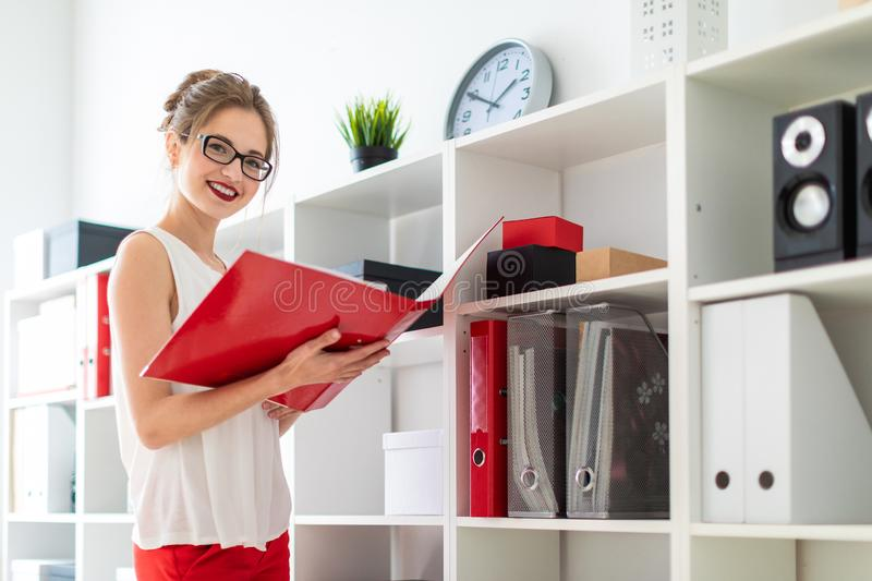A young girl stands near the shelf and holds a red folder in her hands. Beautiful young girl in glasses and a white blouse is working in the office. photo with stock photo