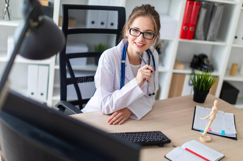 A young girl in a white robe sits at a computer desk and holds a pencil in her hand. A beautiful young girl with glasses and a white coat is working in her stock photos