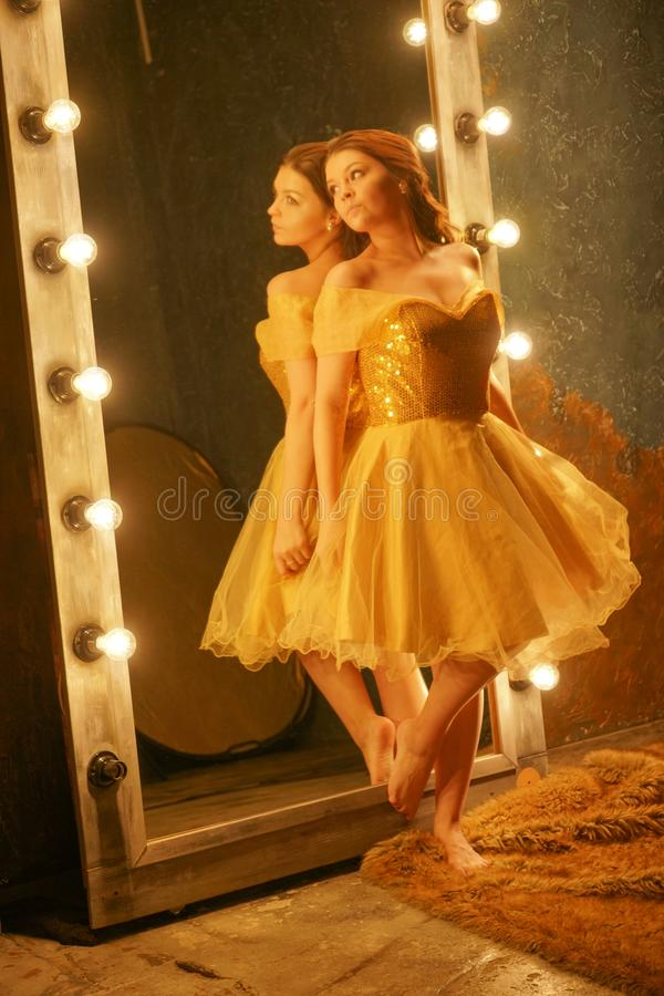 Beautiful young girl in a gold evening dress stands on a fur rug near a large mirror in a frame with lights and looks into her ref. Lection alone royalty free stock image