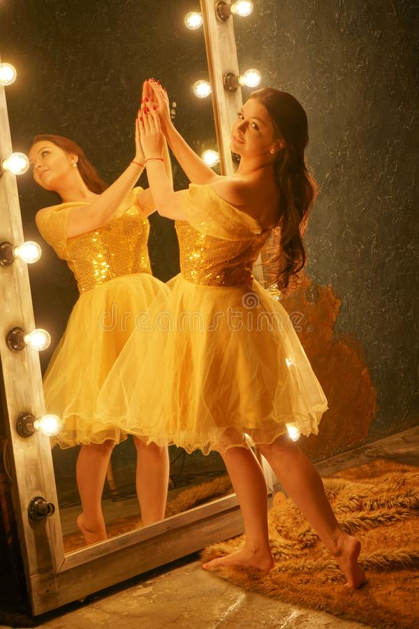 Beautiful young girl in a gold evening dress stands on a fur rug near a large mirror in a frame with lights and looks into her ref. Lection alone stock photo