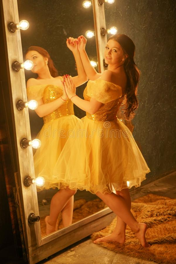 Beautiful young girl in a gold evening dress stands on a fur rug near a large mirror in a frame with lights and looks into her ref. Lection alone royalty free stock photos