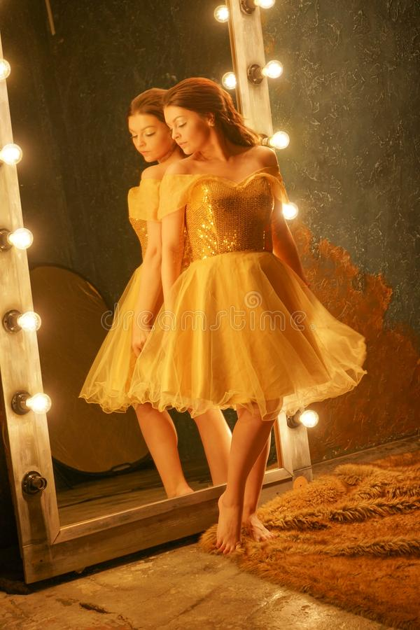 Beautiful young girl in a gold evening dress stands on a fur rug near a large mirror in a frame with lights and looks into her ref. Lection alone royalty free stock photo
