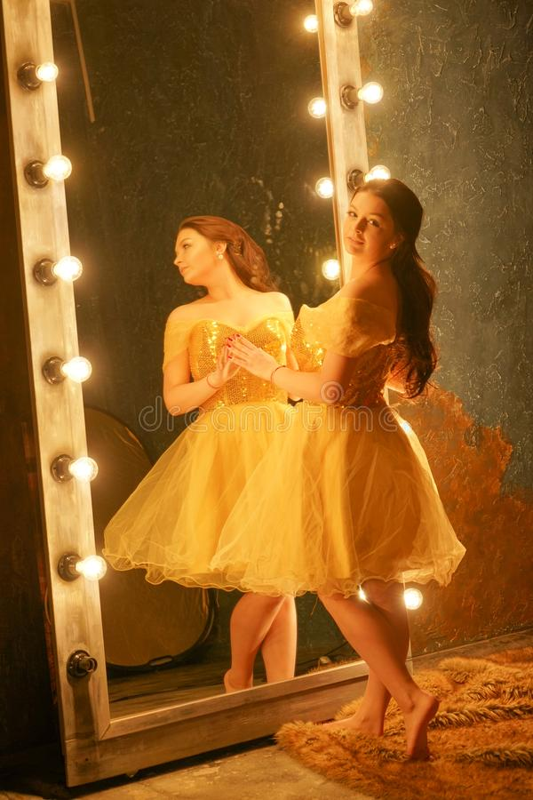 Beautiful young girl in a gold evening dress stands on a fur rug near a large mirror in a frame with lights and looks into her ref. Lection alone stock images