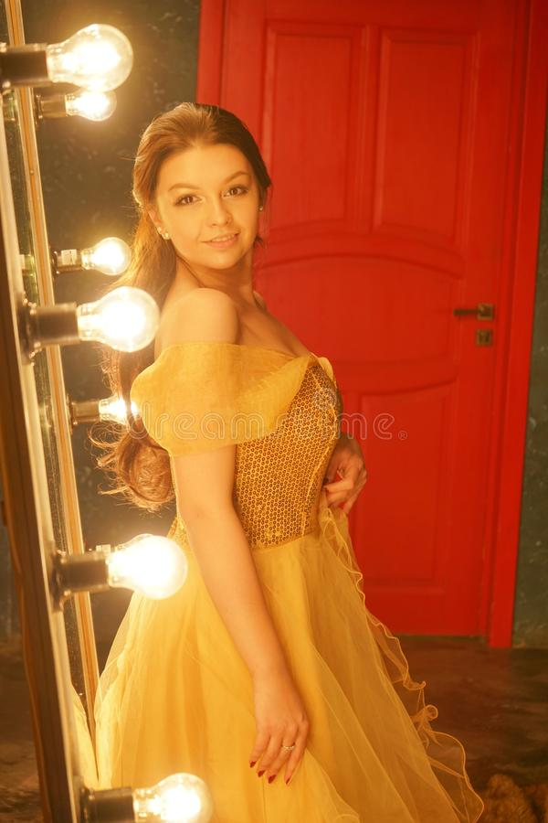 Beautiful young girl in a gold evening dress stands on a fur rug near a large mirror in a frame with lights and looks into her ref. Lection alone stock photography