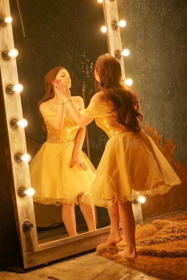 Beautiful young girl in a gold evening dress stands on a fur rug near a large mirror in a frame with lights and looks into her ref. Lection alone royalty free stock images