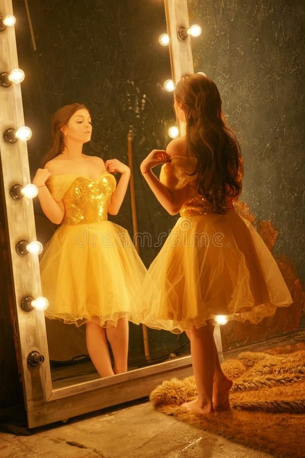 Beautiful young girl in a gold evening dress stands on a fur rug near a large mirror in a frame with lights and looks into her ref. Lection alone stock image