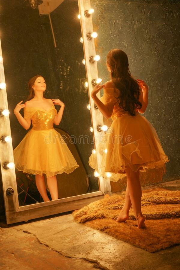 Beautiful young girl in a gold evening dress stands on a fur rug near a large mirror in a frame with lights and looks into her ref. Lection alone stock photos