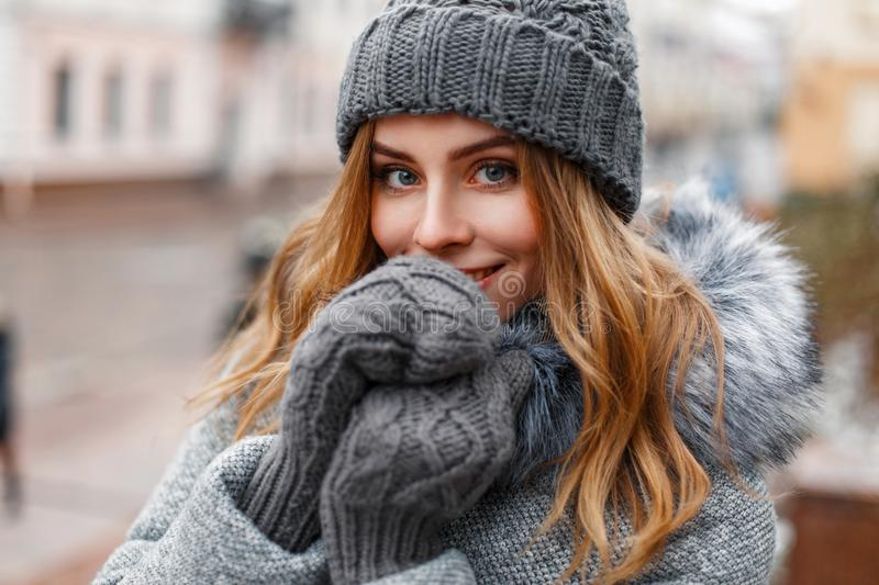 Beautiful young girl in a gray knitted hat and mittens, outdoors. stock image