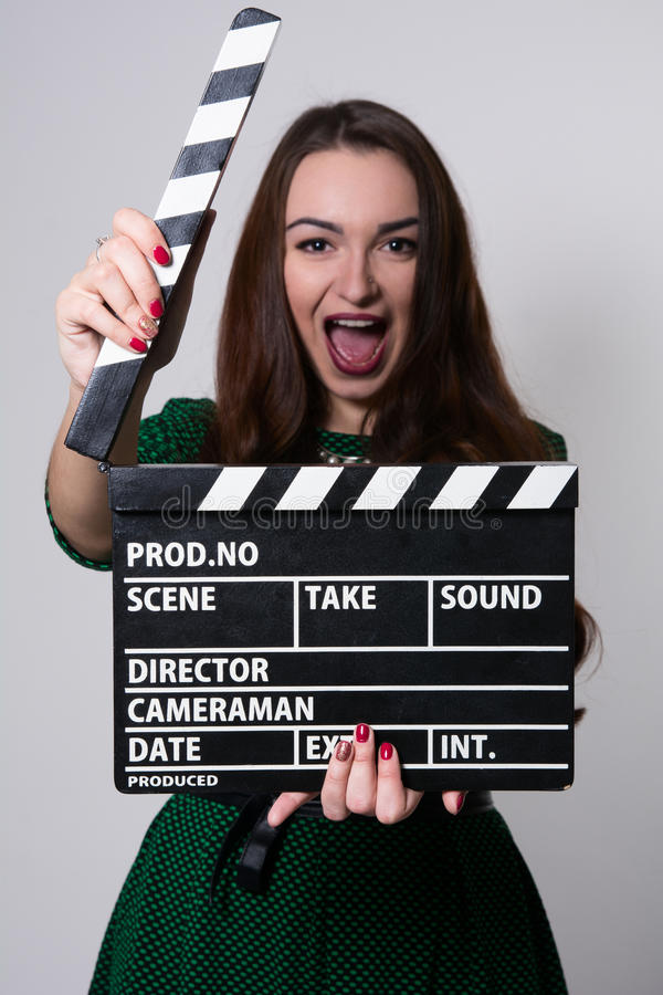 Beautiful young girl in green dress is holding a clapperboard. Looking at camera and shouts, standing against blackboard stock photos