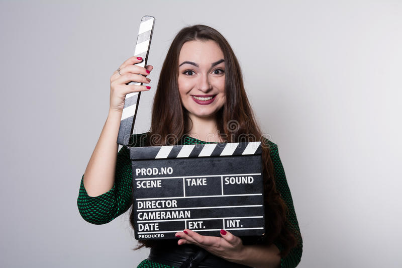 Beautiful young girl in green dress is holding a clapperboard. Looking at camera and smiling, standing against blackboard stock photography