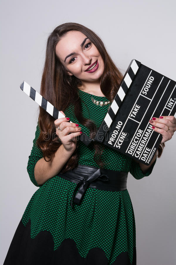 Beautiful young girl in green dress is holding a clapperboard. Looking at camera and smiling, standing against blackboard stock image