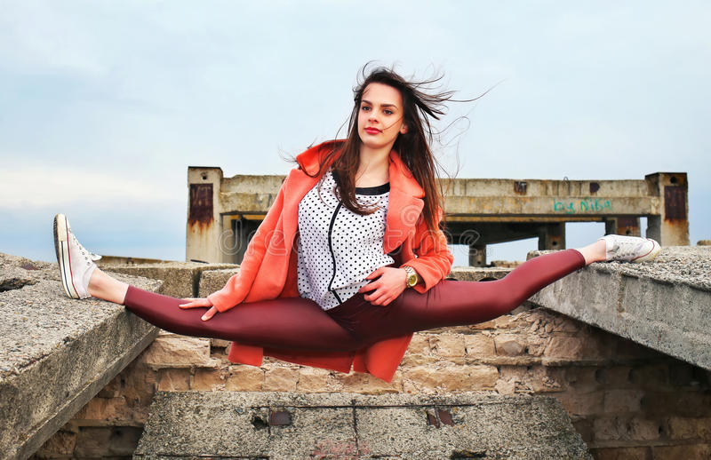 Beautiful young girl gymnast took the pose of twine. On an abandoned building. Fashion and Sports stock photography