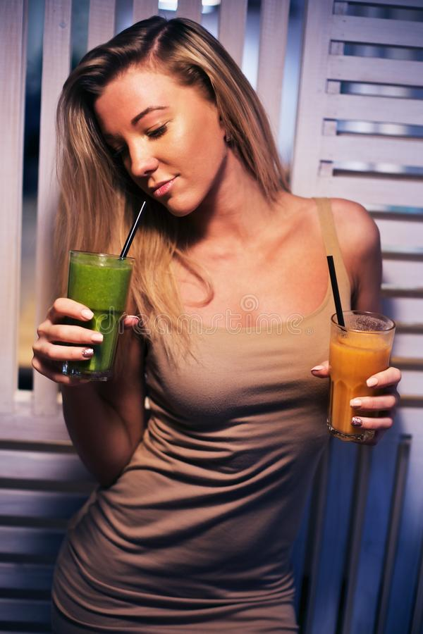 Beautiful young girl in a health cafe drinking smoothies. Go vegetarians. Healthy life with nature products. Beautiful young girl in a health cafe drinking stock photography