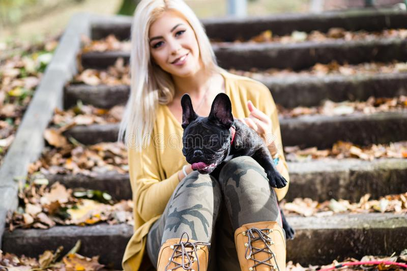 Beautiful young girl with her dog in autumn park stock photos