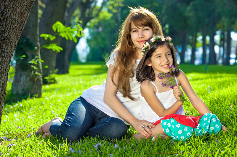 Beautiful young girl with her mother on lush grass royalty free stock photo