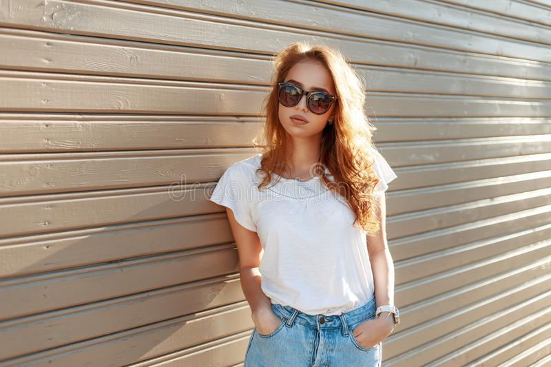 Beautiful young girl in high waist jeans near the vintage royalty free stock photos