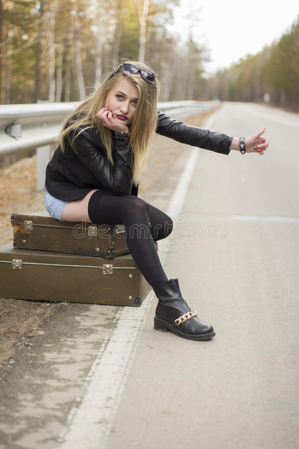 Beautiful young girl hitchhiking. In the United States and Canada royalty free stock photo