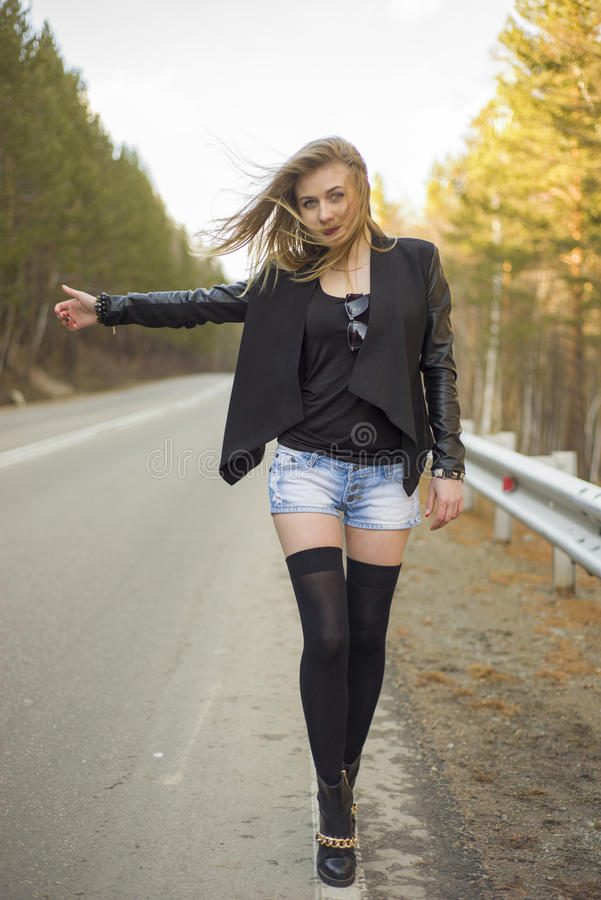 Beautiful young girl hitchhiking. In the United States and Canada royalty free stock image